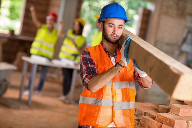 Construction worker bring timber at building site