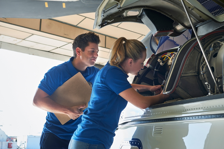 Aero engineer and apprentice working on a helicopter in a hangar.