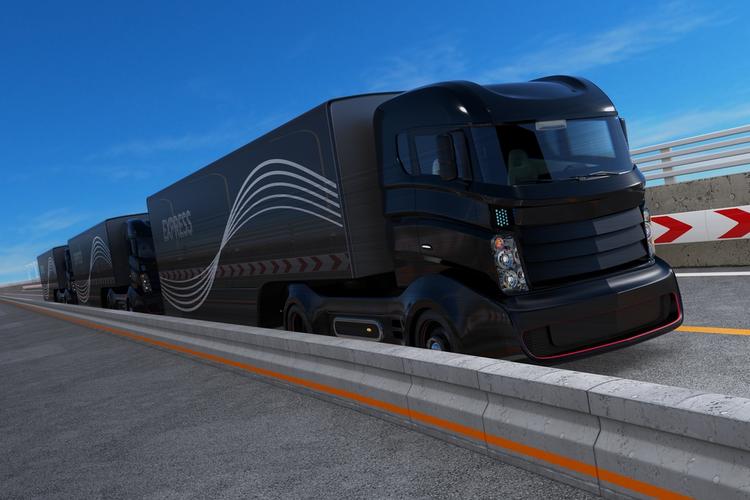 Fleet of autonomous hybrid trucks driving on highway.