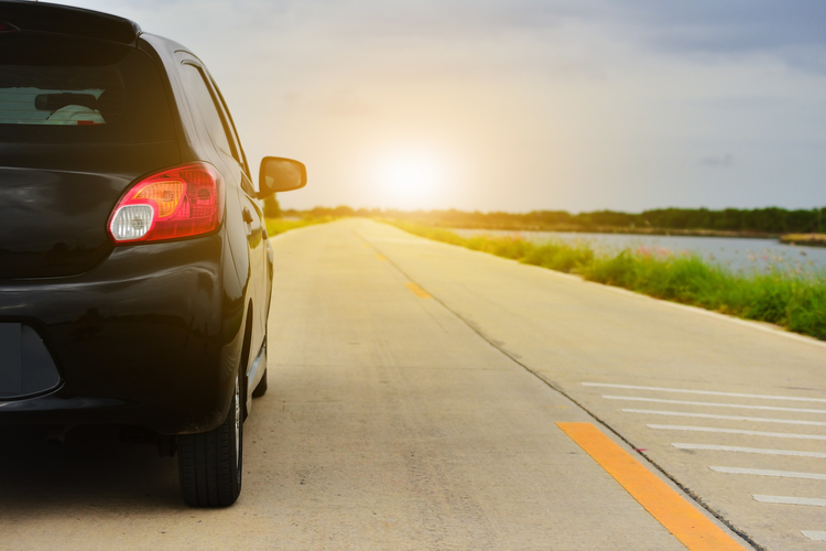 Car parked on road with sun and open highway in background.