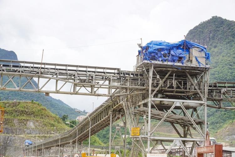 Overhead conveyor belt for concrete transportation on a construction site.