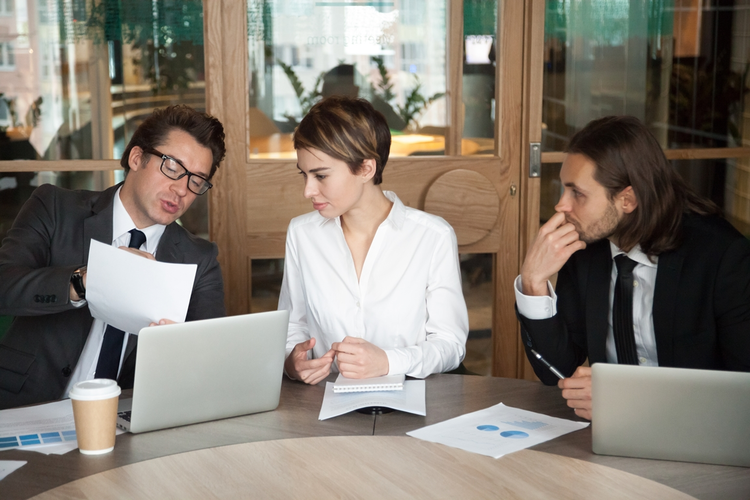 Three colleagues at a table analyzing company data