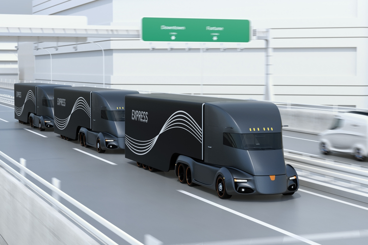 A fleet of black self-driving electric semi trucks driving on a highway.
