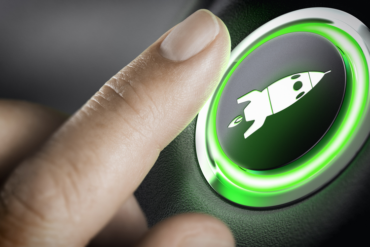 Man's finger pressing an boost button with a rocket icon, black background and green light.
