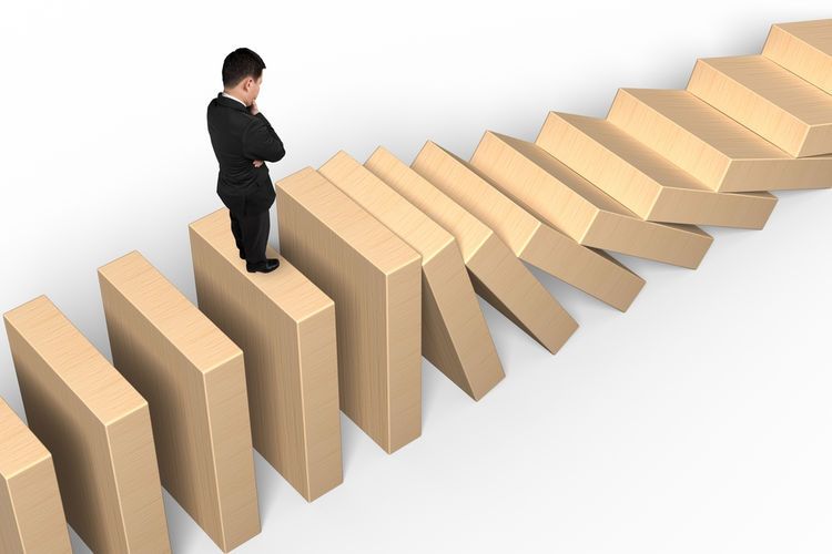 Businessman standing on top of falling columns: Domino effect concept.