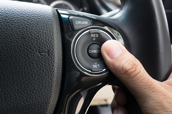 Driver in car pushing cruise control button on steering wheel