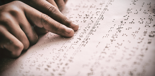 The fingers of someone reading a page in braille