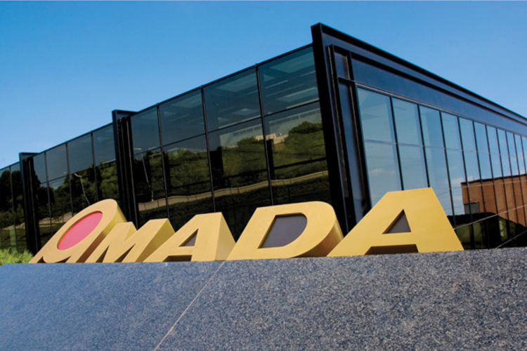 Amada logo in front of building.