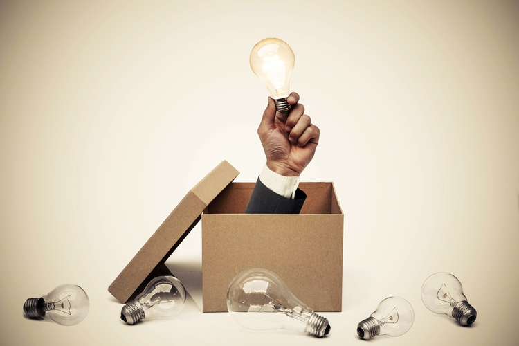 Hand in cardboard box holding light bulb representing innovation
