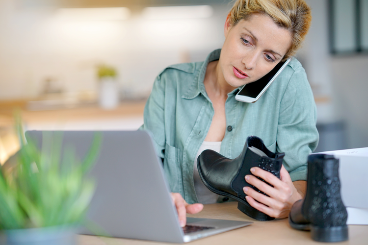 Woman on laptop and mobile phone holding shoes purchased online