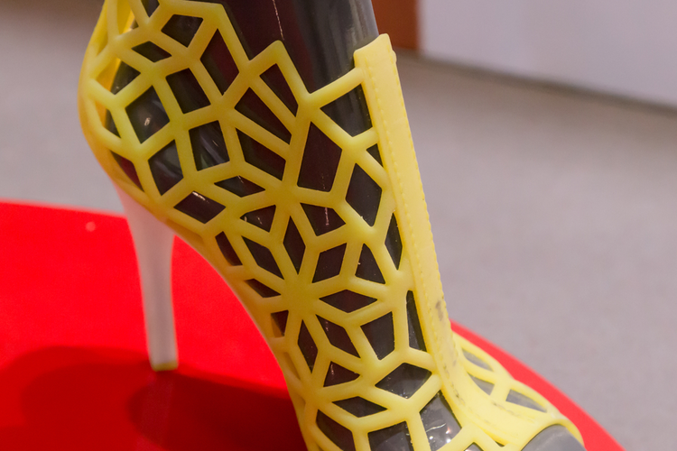 Yellow 3D printed fashion shoe on a mannequin's foot