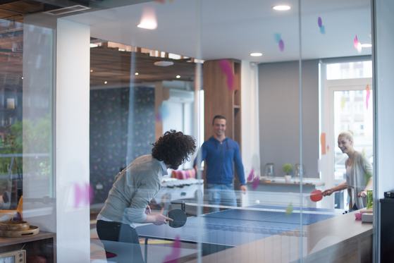 Coworkers playing ping pong in a startup office