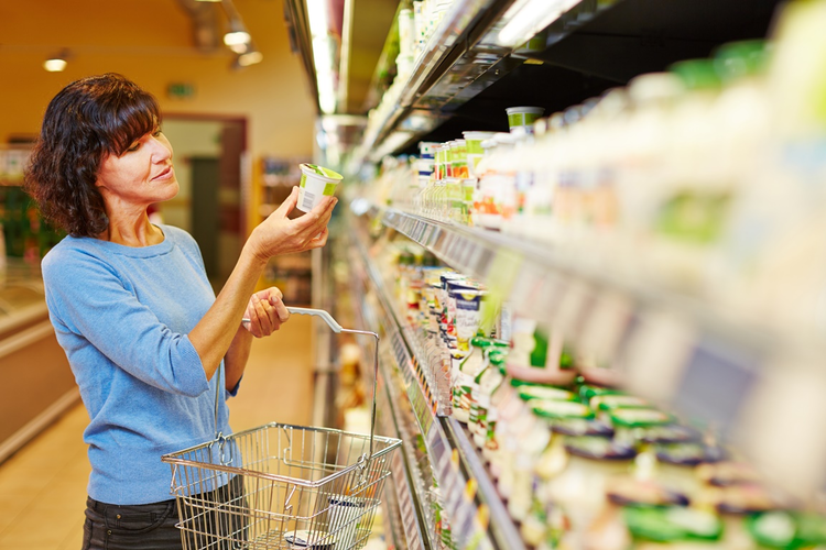 Woman in supermarket examining product label