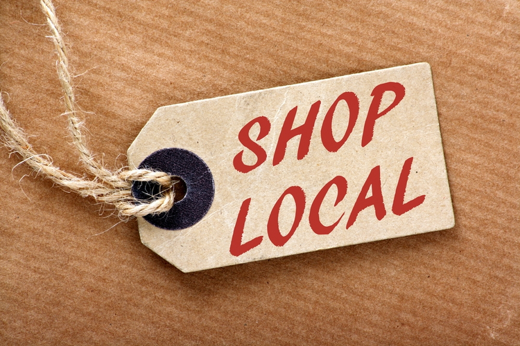 The words 'Shop Local' in red text on a brown paper price label.