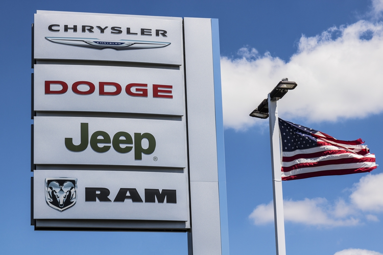 Logo and dealership signage of the four subsidiaries of FCA - Chrysler, Dodge, Jeep, and Ram Trucks in front of American flag.