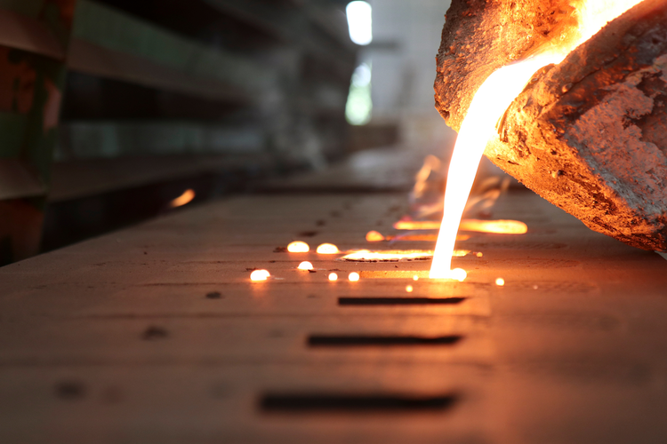 Molten iron being poured into mold during sand casting process