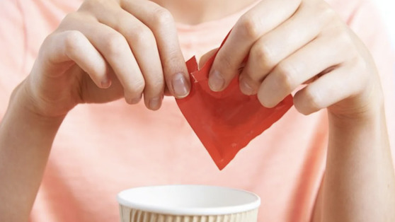 Person opening a sugar packet to add to a cup of coffee