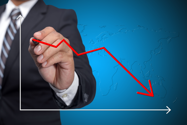 Business man drawing decline graph over blue background.