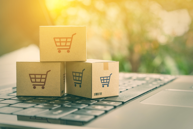 Online shopping/e-commerce and delivery service concept: Paper cartons with a shopping cart on a laptop keyboard.