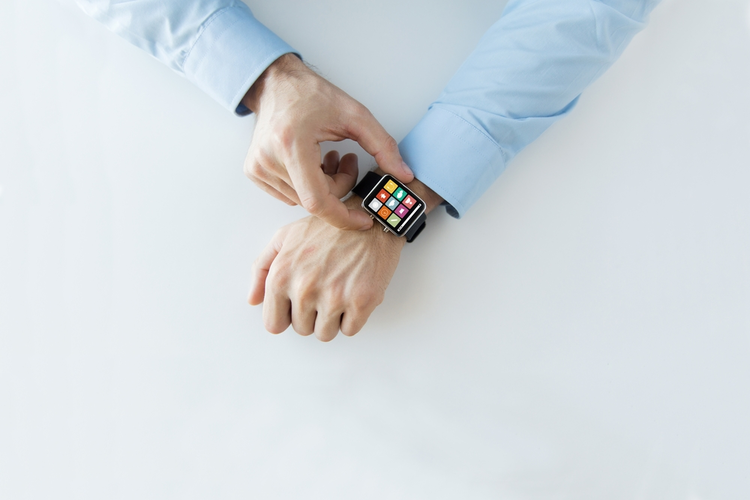 Hands setting smart watch with application icons on screen.