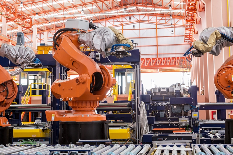 Three welding robots in manufacturing facility