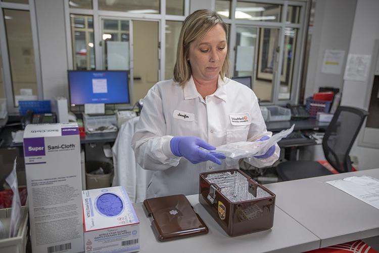 Laboratory technician prepares a sample to be shipped via drone