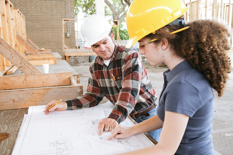 Trade school student learning to read construction blueprints.