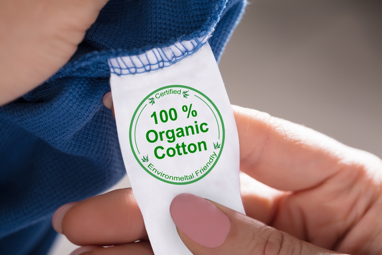 Close-up of a person's hand holding label showing 100 percent organic cotton.