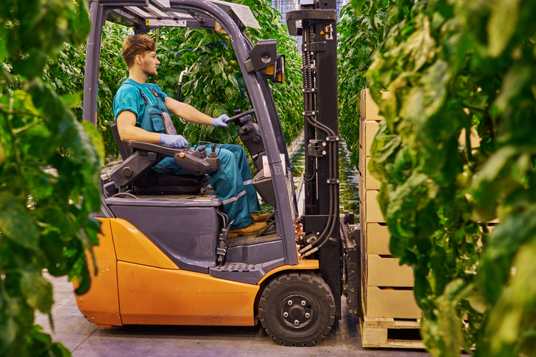 A forklift driving past greenery