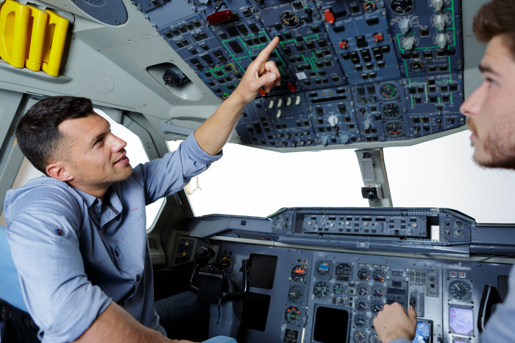 Two people in aerospace training pointing at power switches