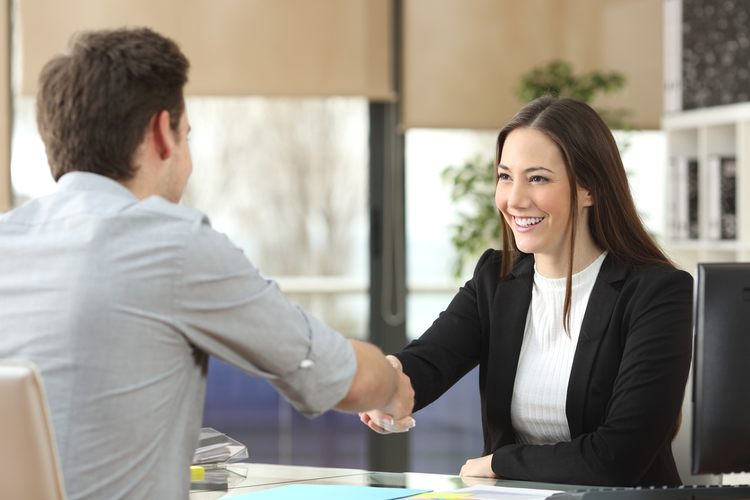 Businesswoman shaking hands with client.