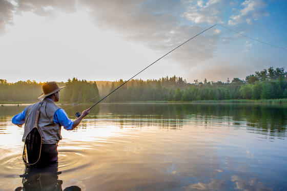 A man fly fishing at sunrise
