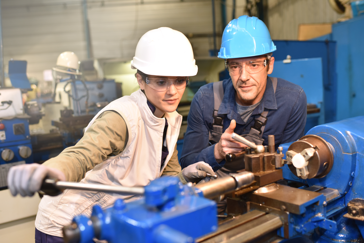 Two metalworkers in a manufacturing facility