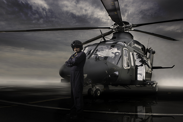 Pilot standing in front of a MH-139 helicopter.