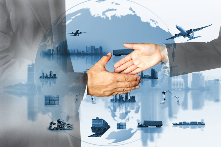 Business professionals shaking hands in front of supply chain concept.