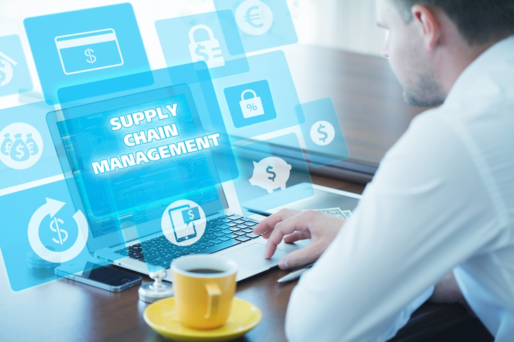 Business man clicking on laptop with virtual Supply Chain Management icon.