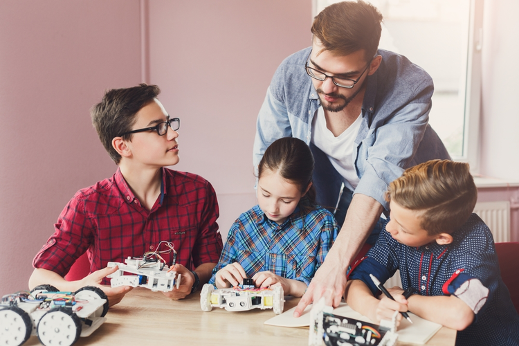 STEM education: Kids creating robots with teacher.