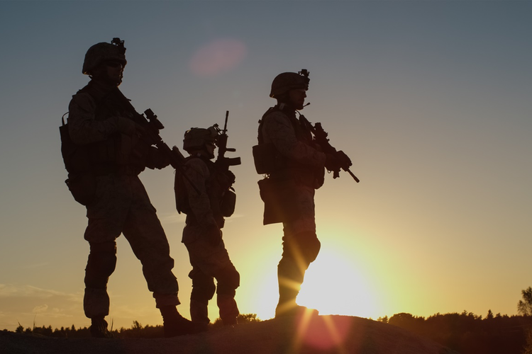 Soldiers with gear at sunset