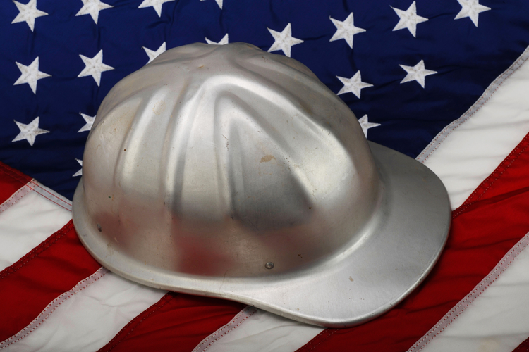 Silver hard hat laid over an American flag
