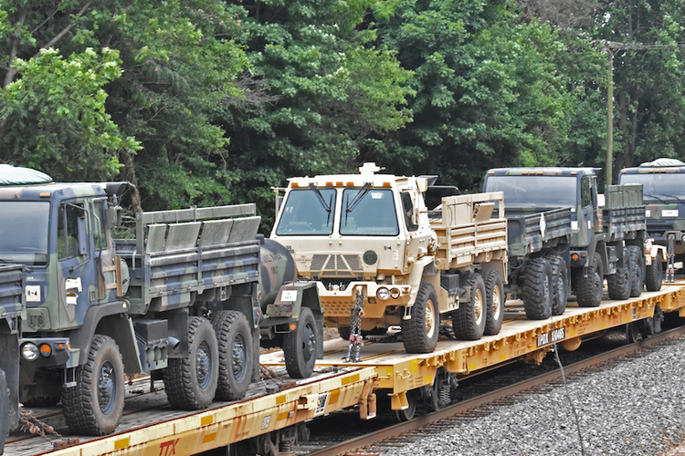 Military vehicles being transported by train