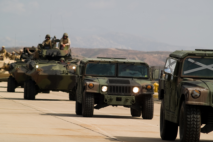 Marines in armored military trucks driving down a road