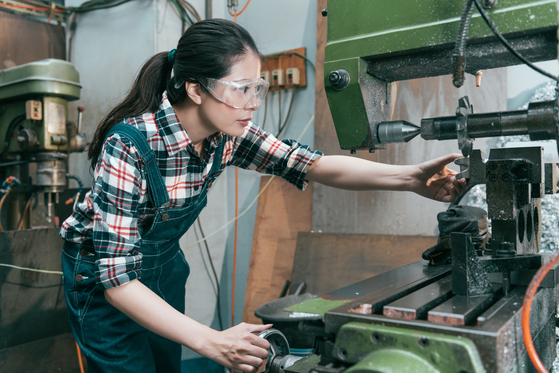 Woman in an industrial manufacturing role working on production