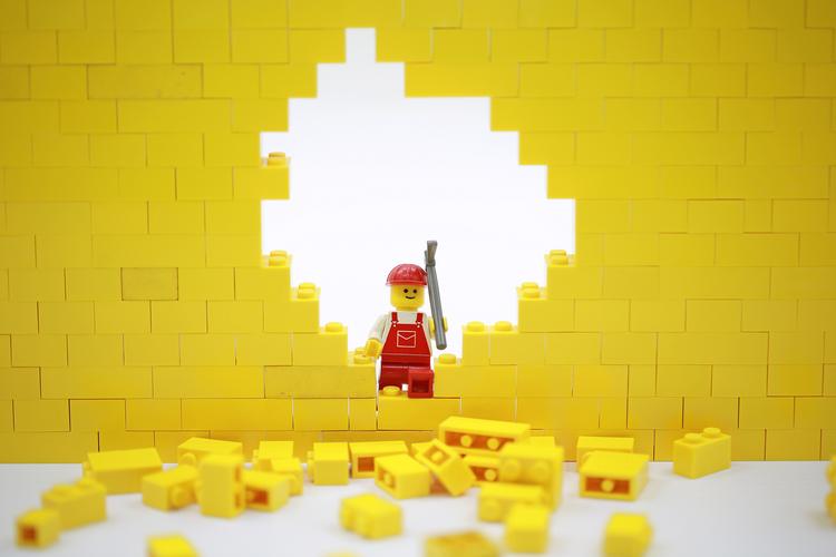Lego person breaking through Lego wall