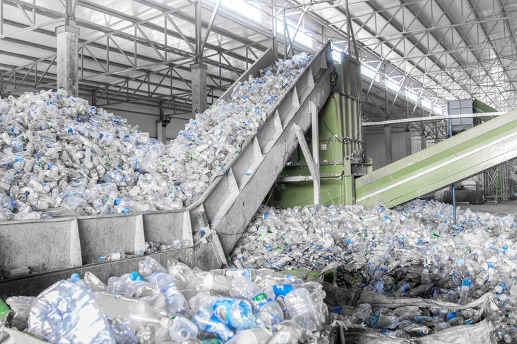 Plastic recycling plant with piles of single-use plastic water bottles.