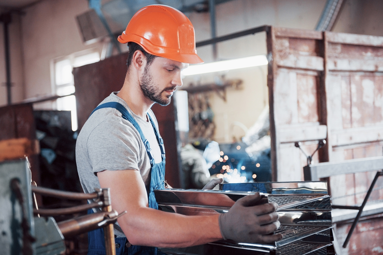 Young worker wearing a hardhat in a metalworking facility