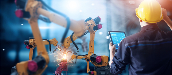 Man with tablet observing industrial robotic arms in action
