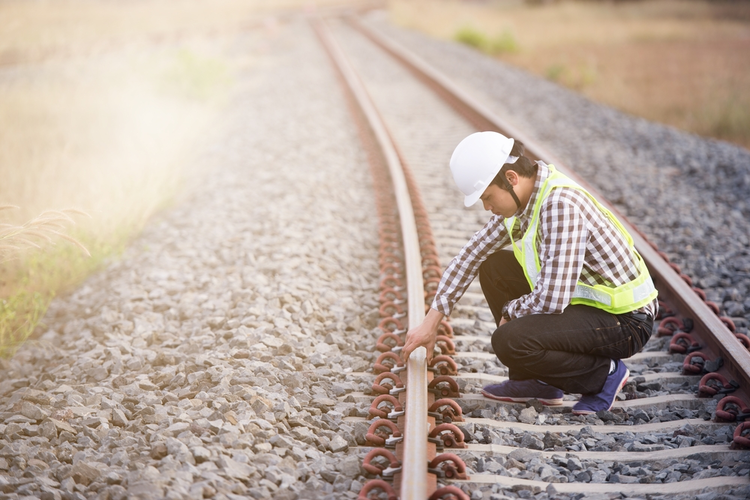 Railroad worker checking railway.
