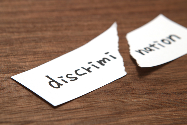 Piece of paper with the word discrimination written on it torn in half, indicating the end of discrimination