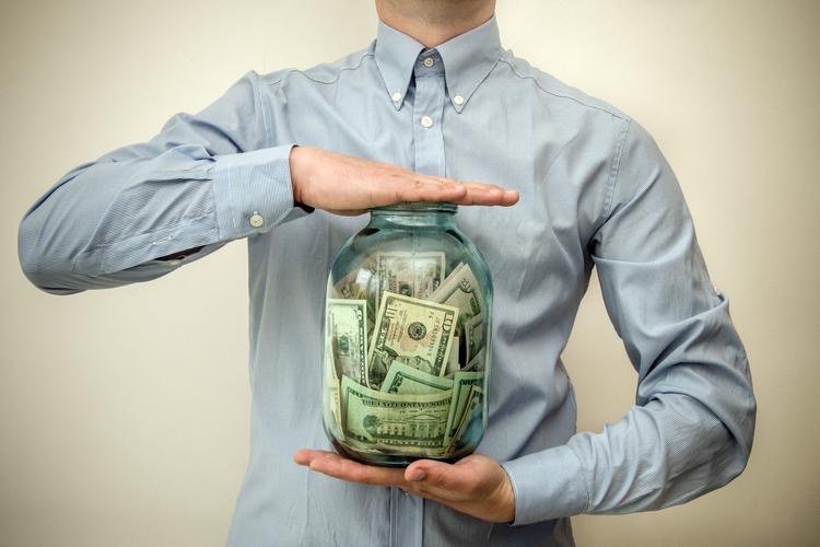 Man holding jar of money