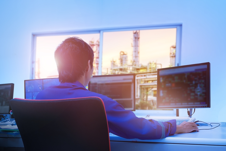 Technician sitting in a control room monitoring a process petrochemical plant.